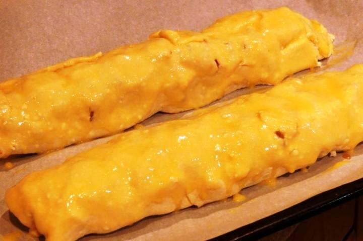 Рулеты смажьте сверху желтком и отправьте в разогретую до 200 градусов духовку на полчаса. Готовые рулеты остудите, посыпьте сахарной пудрой и подавайте на стол.