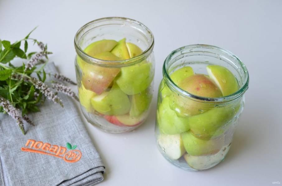 2. Яблоки порежьте на 4 части, удалите сердцевинки. Плотно уложите в стерильные банки.