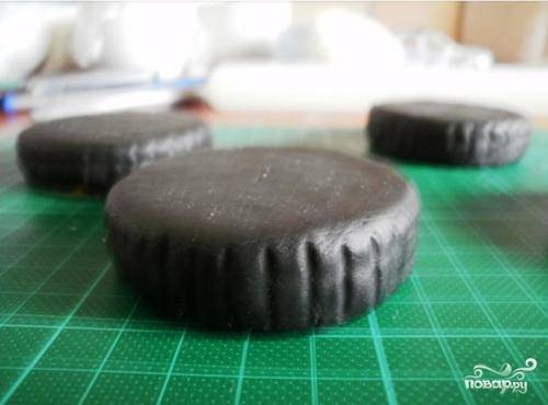 Теперь нам надо сделать колеса. Можно их сделать из  печенья круглой формы и обмотать его мастикой, которую подкрасил в черный цвет. Окна делаем тонированные :).