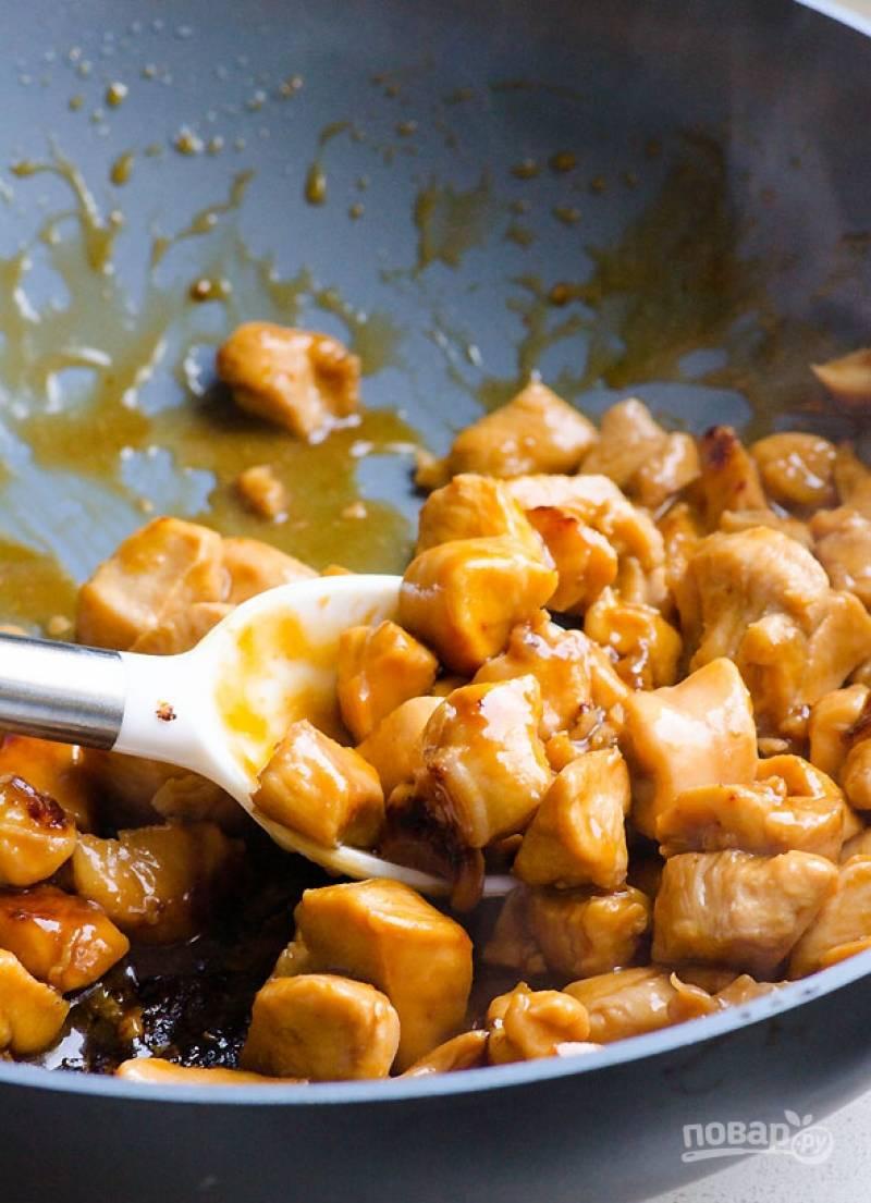 Курицу достаньте из маринада и отправьте в глубокую сковороду, обжарьте до золотистого цвета. В миску с маринадом добавьте оставшийся соевый соус, ложку меда, крахмал и воду, взбейте все до однородности. Добавьте соус к курице, протомите 10 минут.