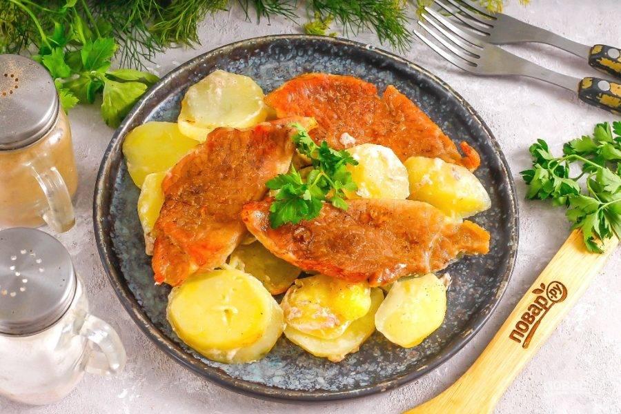 Выложите на тарелку ломтики картофеля, а на них запеченное мясо и подайте к столу. Помните, что картофель после запекания станет очень мягким. Не забудьте дополнить блюдо свежей зеленью, соленьями или квашеными овощами. Приятного аппетита!