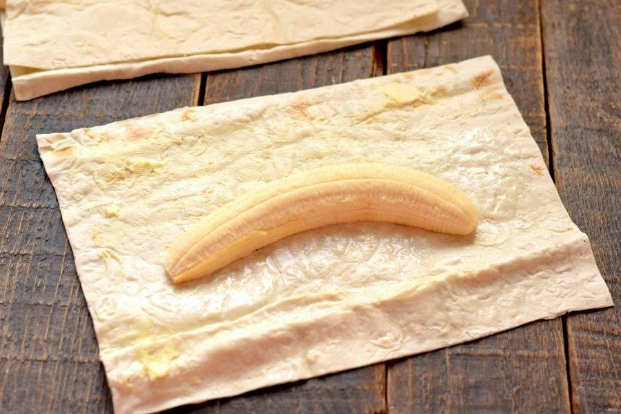 В середину лаваша выложите половинку банана. Если банан имеет очень изогнутую форму, его можно разрезать поперек на две части, так его будет удобнее свернуть в лаваш.