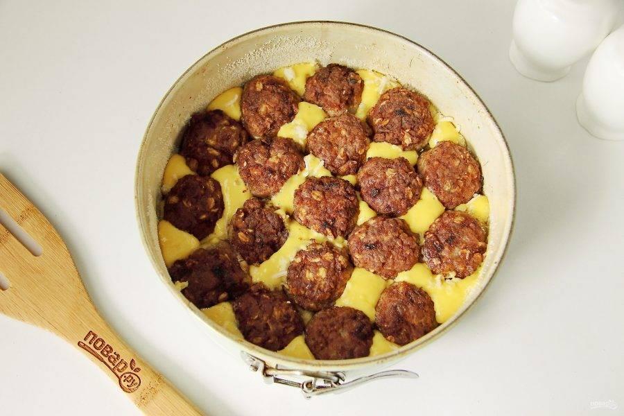 Сверху посыпьте тесто немного тертым сыром и вдавите в тесто фрикадельки.