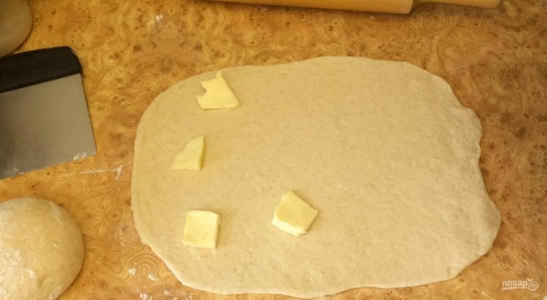 4.  Округлите их и раскатайте в прямоугольник средней толщины. Равномерно распределите мягкое сливочное масло по тесту. Сверните тесто в рулет, затем – улиткой. Переложите тесто в пакет и положите в холодильник на 1 час.