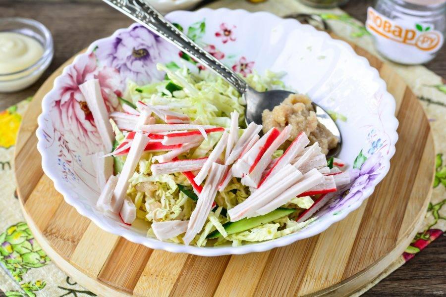Нарежьте крабовые палочки полосками и всыпьте в салат. Также добавьте пару ложек соленой икры мойвы.