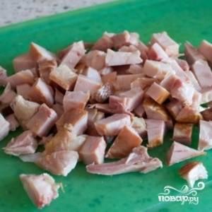 Затем добавьте в сковороду вино и оставьте на огне на 2 минуты. После этого переложите овощи в кастрюлю, добавьте бульон, нарезанную кубиками картошку и майоран. Доведите до кипения, убавьте огонь и оставьте под крышкой на 15 минут. Добавьте кукурузу и оставьте на 5 минут. Тем временем нарежьте копченую курицу кубиками.