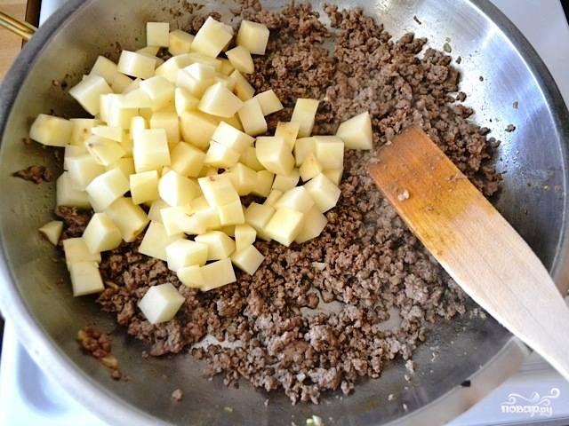 Когда специи достаточно обжарятся, добавляем в жаровню говяжий фарш. Обжариваем фарш до румяности, после чего добавляем картофель.