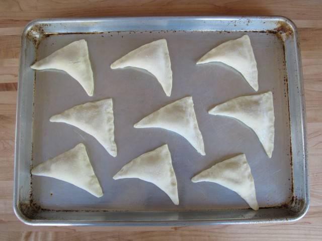 6. Противень застелите пергаментной бумагой или смажьте растительным маслом. Выложите пирожки с творогом.