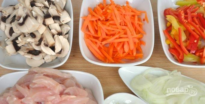 Морковь нарезаем соломкой, грибы - ломтиками, курицу и болгарский перец - полосками. Лук и чеснок мелко рубим.