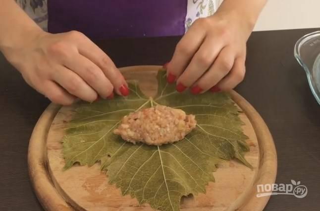 9. Виноградный лист положите вниз блестящей стороной. В каждый голубец понадобится ложка фарша. Заверните лист так же, как и при готовке обычных голубцов.