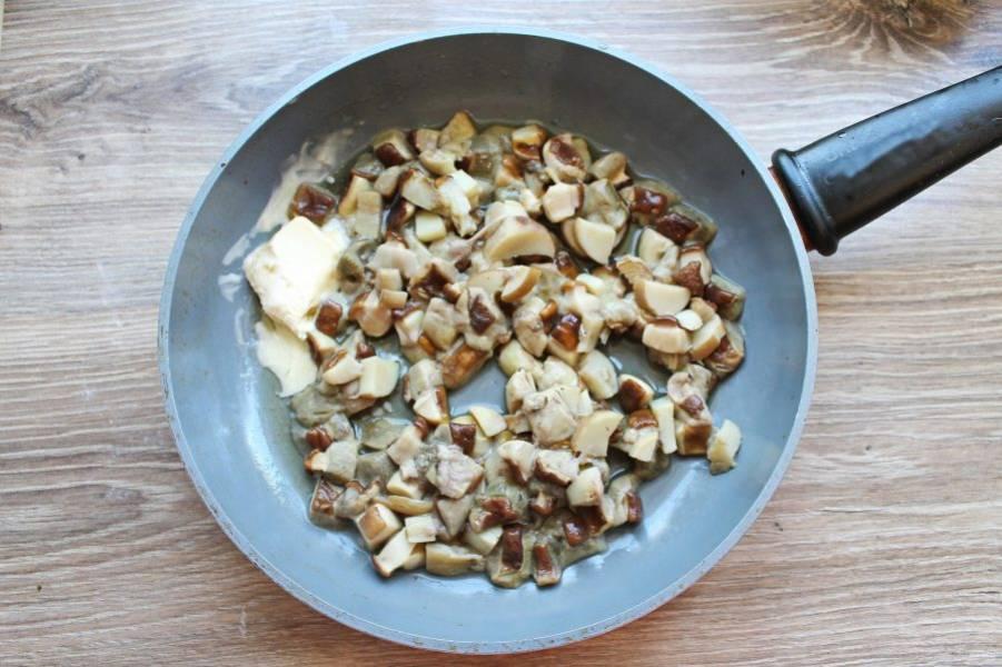При помощи сита достаньте отварные грибы и выложите в сковороду, добавьте сливочное масло. Обжаривайте на среднем огне в течение 10 минут, перемешивая.