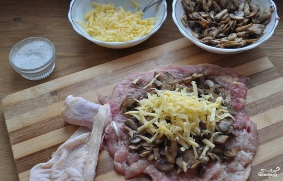На мясо уложите начинку из сковороды. Сверху натрите сыр на крупной тёрке.