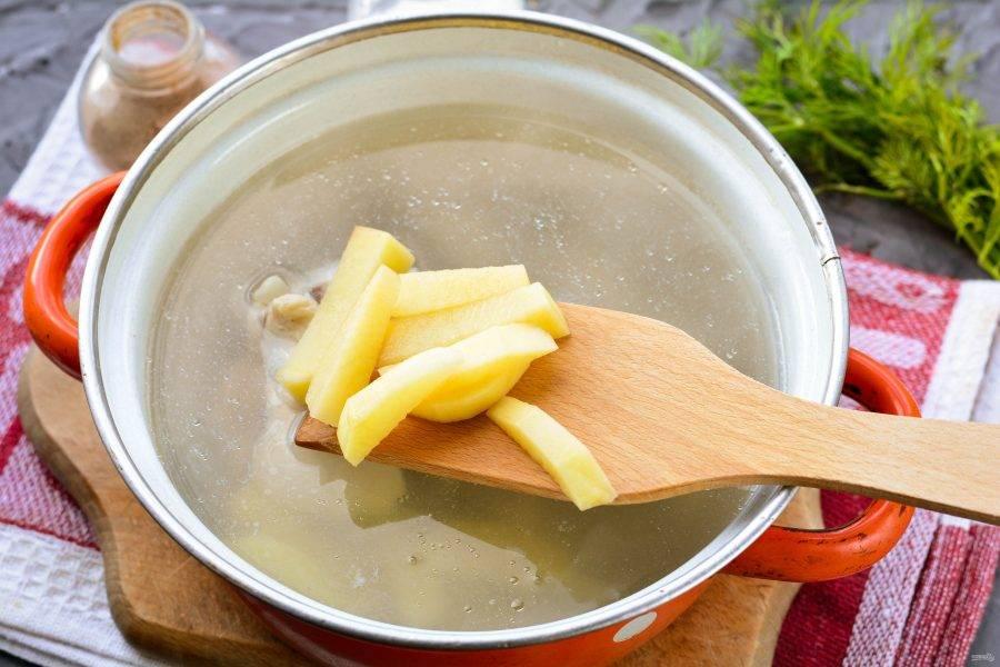 Сварите куриный бульон. Опустите промытую курицу в холодную воду, варите после закипания на медленном огне 15-20 минут. Посолите по вкусу. Достаньте курицу из бульона, отделите мясо от костей. Верните мясо обратно в кастрюлю. Всыпьте в готовый куриный бульон картофель. Варите 5-7 минут.