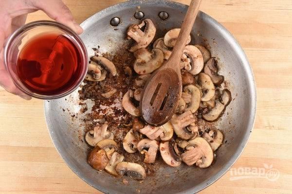 4. После этого обжарьте в оставшимся жире из-под сосисок грибы с луком в течение 5 минут. Потом к ним добавьте красный перец и влейте вино. Готовьте ещё пару минут.
