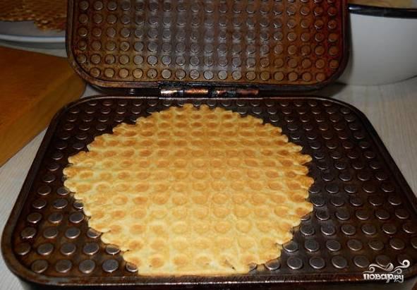 3.Разогрейте электрическую вафельницу. На центр положите ложку теста и выпекайте минуту. Готовую вафлю быстро снимите с вафельницы и сверните в трубочку.