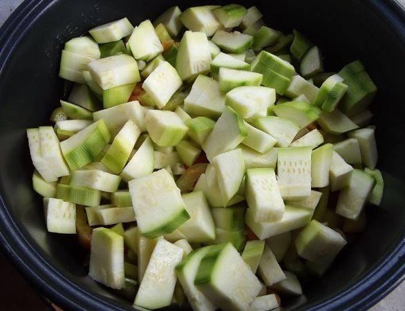 Выкладываем в чашу мультиварки к луку и помидорам перец, чеснок, отжатые от сока баклажаны, кабачки.