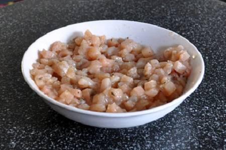 5. Грудку вымойте и обсушите бумажным полотенцем. Нарежьте маленькими кубиками. Очистите половинку луковицы (или другие овощи, которые вы решите использовать в рецепт приготовления самсы с курицей), измельчите и добавьте в мисочку. Посолите, поперчите по вкусу, добавьте любимые специи и сушеные травы.