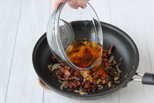7. Затем добавить на сковороду грибной бульон (слитую с грибов воду). Посолить и поперчить по вкусу. Тушить на медленном огне до готовности.