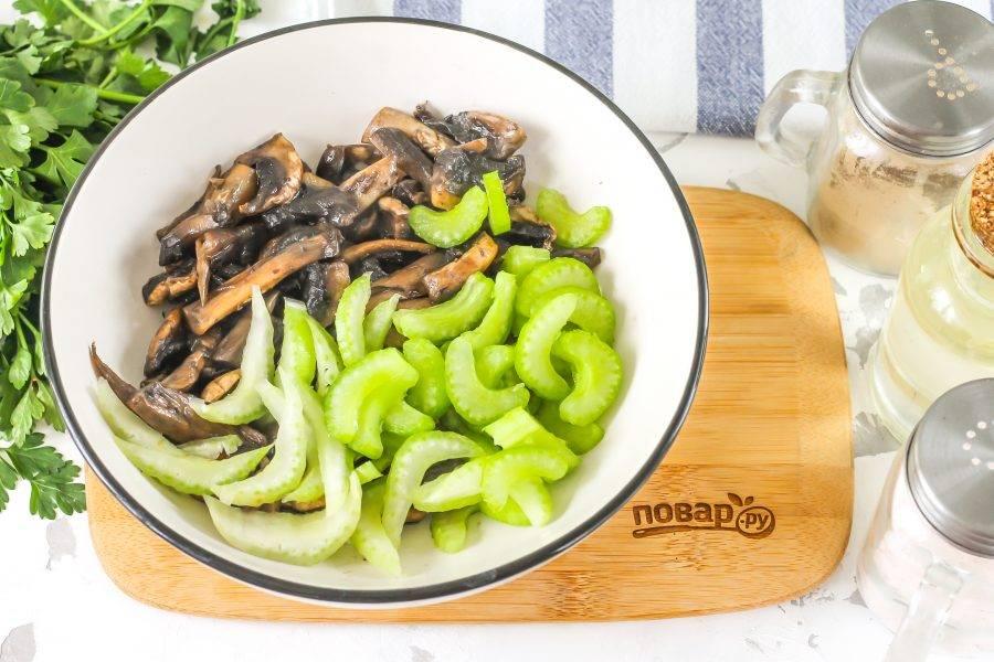 Выложите обжаренные грибы в глубокую емкость. Промойте стебли сельдерея, нарежьте и добавьте туда же.