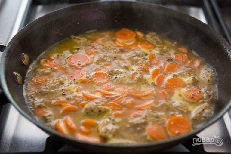 5.Верните сковороду на огонь. Выложите морковь, нарезанную тонкими кружочками. Залейте морковь жидкой смесью без крахмала. Доведите все до кипения и тушите 5-7 минут, затем выложите свинину.