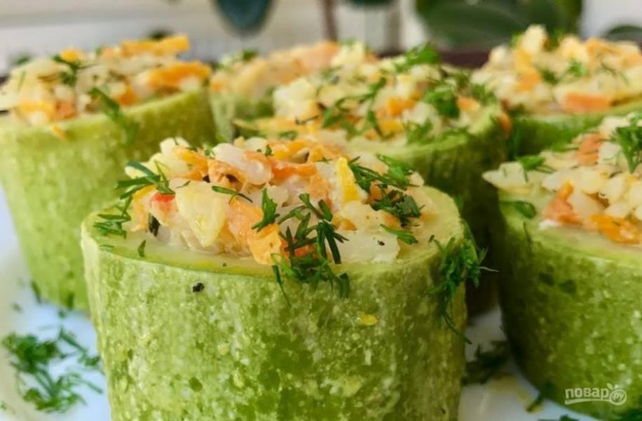 4.  Половину мякоти кабачков мелко порубите и добавьте к начинке. Начините кабачки ложкой и выложите в мультиварку. Налейте немного воды (100 мл) в мультиварку, выставите режим «Запекание» и запекайте овощи в течение 25 минут. Приятного аппетита!