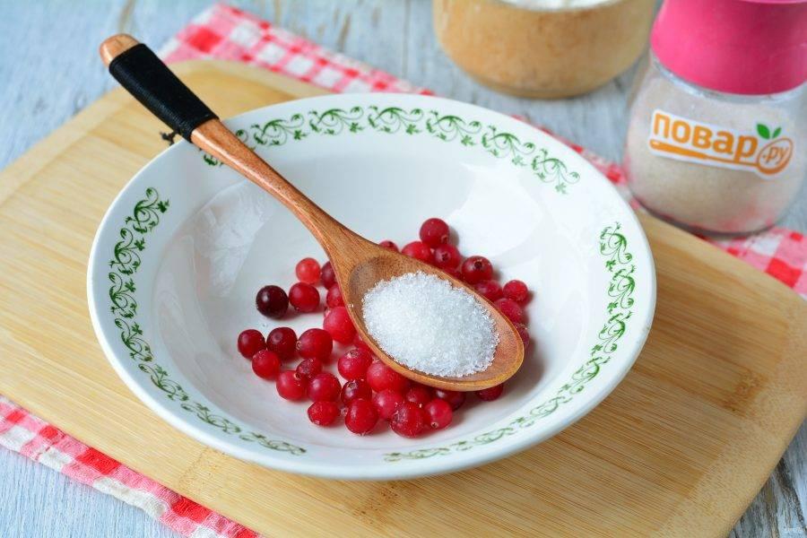 Для начинки смешайте клюкву с сахаром и перемешайте. Если клюква заморожена, разморозьте ее.