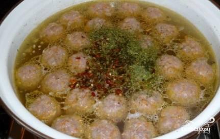 Добавляем картошку в кастрюлю с фрикадельками, солим и добавляем специи и зелень. Варим до готовности картошки.