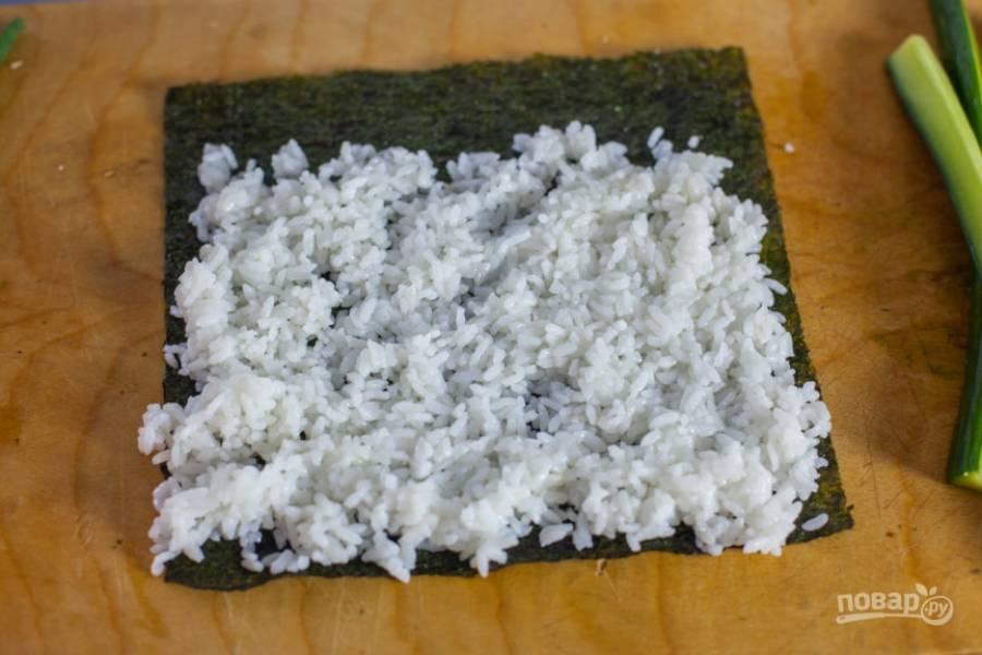 1.Слегка смочите лист водорослей водой, затем выложите часть отварного риса и распределите его по всей поверхности, оставив по 1 см с каждой стороны, а с другой оставьте около 2 см.