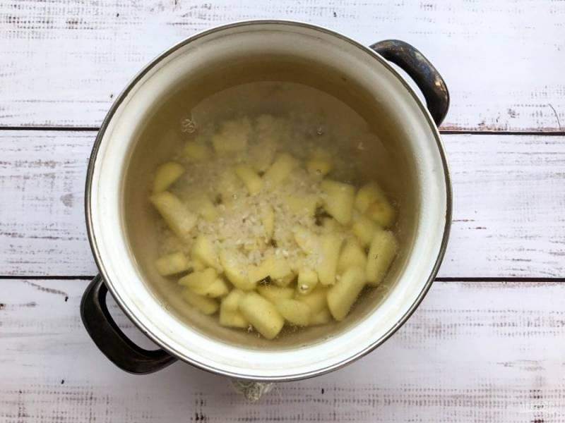 В кипящую воду выложите нарезанный картофель, рис и варите 15 минут.