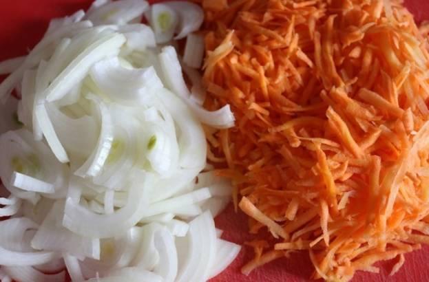 Гречку промойте и пересыпьте в горшочек, в котором будет запекаться блюдо. Залейте гречку горячей водой на 2 см выше крупы. Накройте крышкой и оставьте гречку разбухать на 20-30 минут. Тем временем трем морковь на терке, лук режем полукольцами.