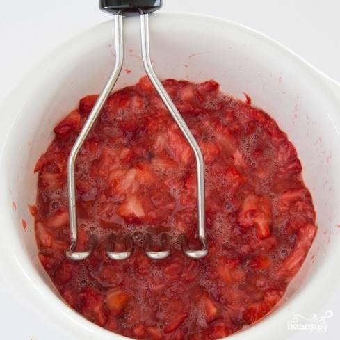 При помощи картофелемялки раздавливаем клубнику. Не пытайтесь сделать это блендером - блендер измельчит все в пюре, а нам надо, чтобы в массе попадались целые кусочки клубники. В этом - вся фишка десерта, поэтому не перестарайтесь с измельчением - нужно всего лишь придавить клубнику, чтобы она дала сок.