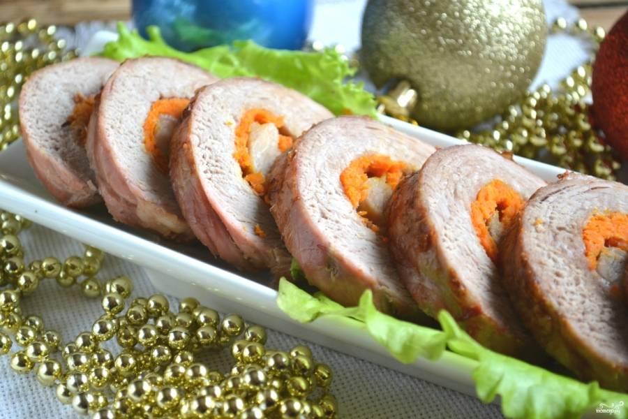 Готовый рулет остудите и нарежьте порционно. Выложите на тарелку, украсьте зеленью и подавайте к праздничному столу.
