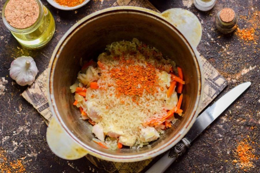 Всыпьте в казан порцию риса. Добавьте соль, перец, куркуму и специи для плова.