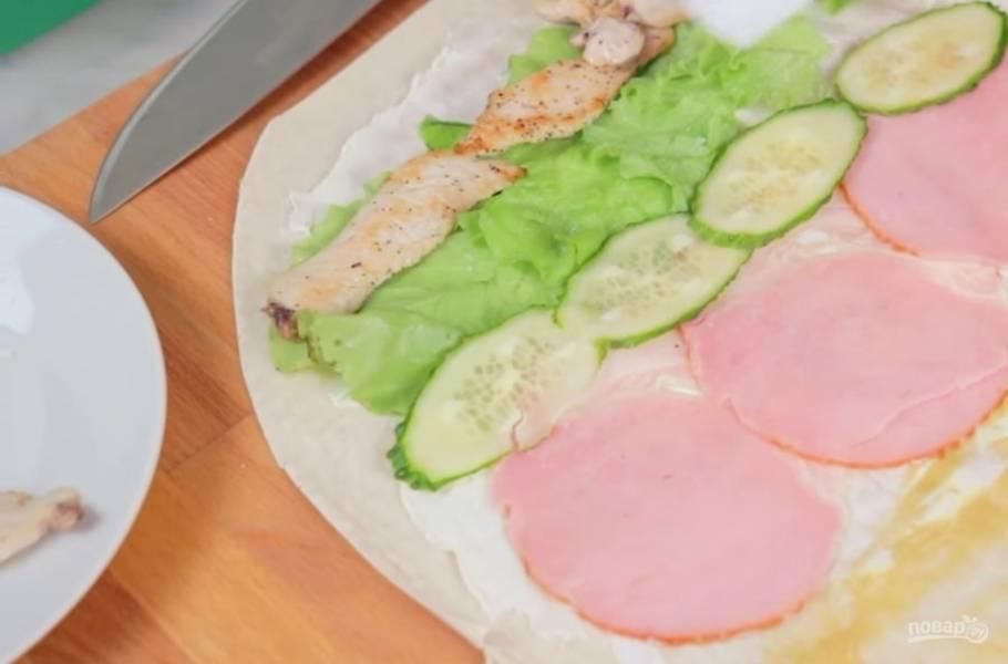 3. Далее выложите на лаваш листья салата, обжаренную куриную грудку, тонко нарезанный огурец и колбасу. Посолите овощи, по желанию добавьте перец и сушеный чеснок.