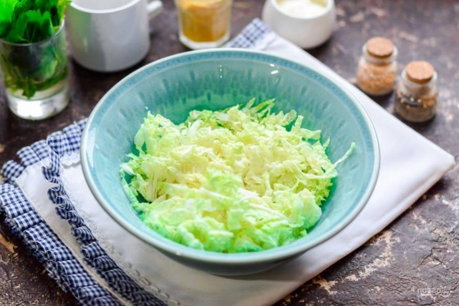 Пекинскую капусту сполосните и нарежьте соломкой, переложите капусту в салатник.