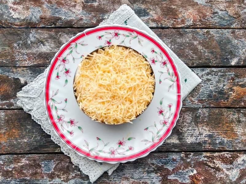 Следующий слой выложите из натертого сыра.