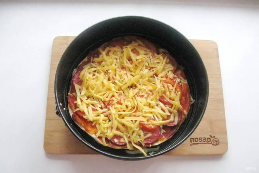 После достаньте пиццу из духовки. Посыпьте  тертым сыром и отправьте опять в духовку до расплавления сыра.