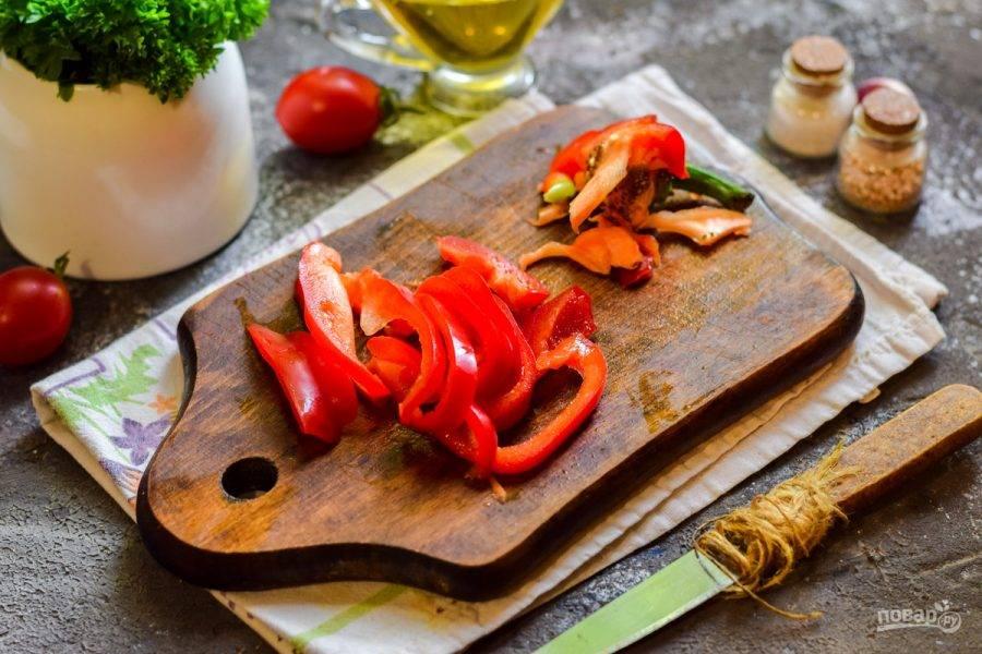 Сладкий перец очистите от семян, сполосните, нарежьте полосками.