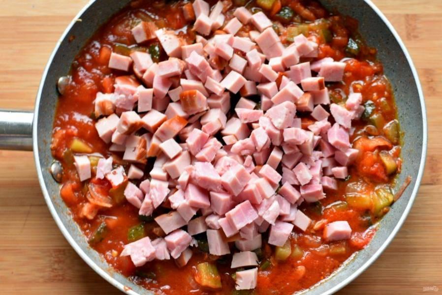Добавьте томатную пасту, прогрейте, затем нарезанные кубиками колбасу и ветчину, прогрейте еще пару минут. Опустите в суп отложенное мясо свинины.