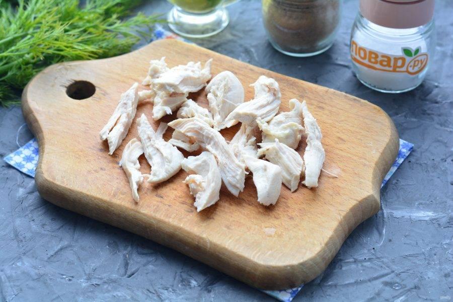 Сварите до готовности куриное филе, варите в подсоленной воде 20-25 минут. Остудите мясо и разберите на средние кусочки.