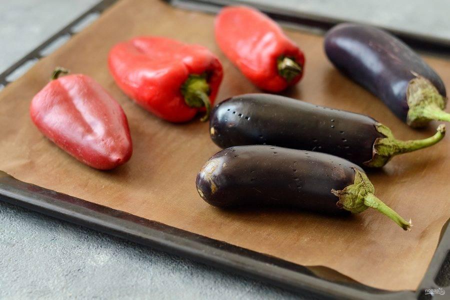 Баклажаны помойте, обсушите, сделайте несколько проколов вилкой. Болгарский перец тоже помойте и обсушите. Выложите овощи на противень и запекайте при температуре 200 градусов. Запекайте баклажаны около часа, а перцы примерно 35-40 минут. Во время приготовления овощи необходимо будет перевернуть пару раз.