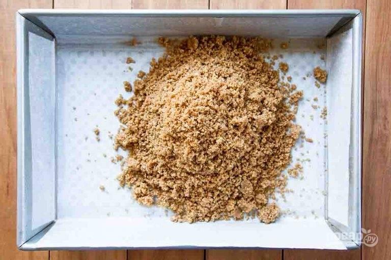 1.Измельчите крекеры. Смешайте в миске крекерные крошки и растопленное сливочное масло. Выложите полученную массу в форму, застеленной пергаментной бумагой.