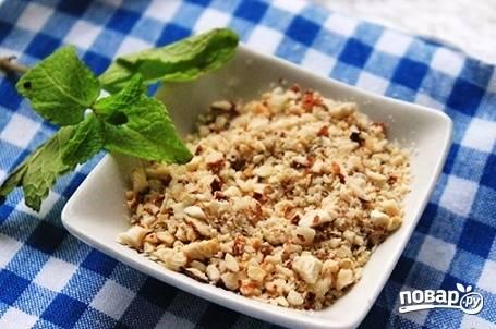 Измельчаем орехи в блендере или рубим мелко ножом. Орехи в салат подойдут любые. Даже лучше, если у вас будет смесь орехов.