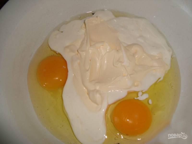 В емкость среднего размера разбейте яйца, добавьте майонез и сметану.