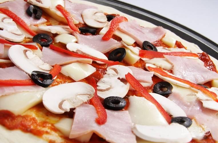 Также тонко нарезаем болгарский перец и маслины. Выкладываем их на тесто.