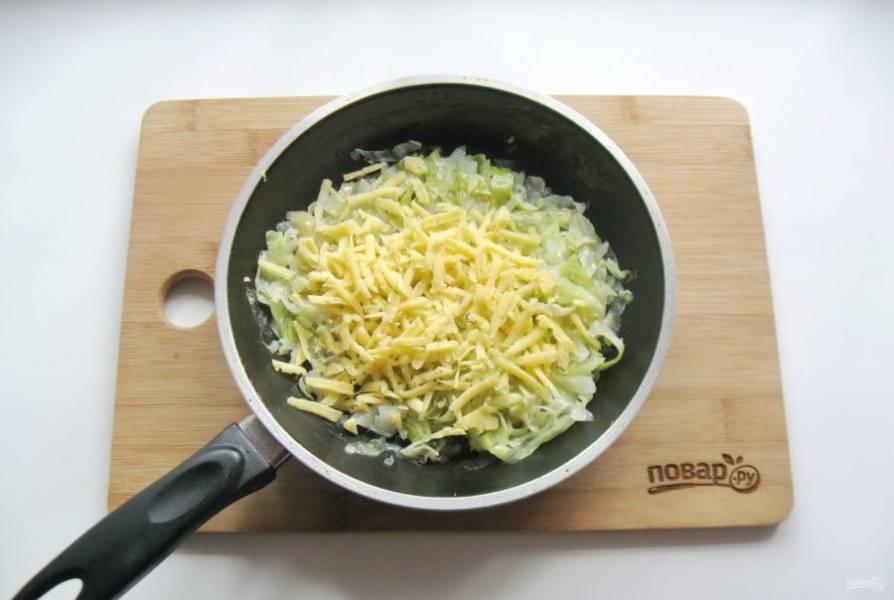 Тушеную капусту с луком остудите и добавьте тертый твердый сыр. Посолите по вкусу и перемешайте начинку.