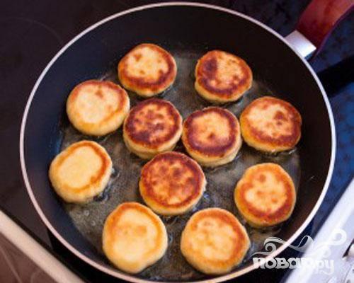 3.Немного масла наливаем в сковороду, разогреваем и выкладываем сюда сырники. На небольшом огне жарим до золотистого цвета. Обжариваем с обеих сторон.