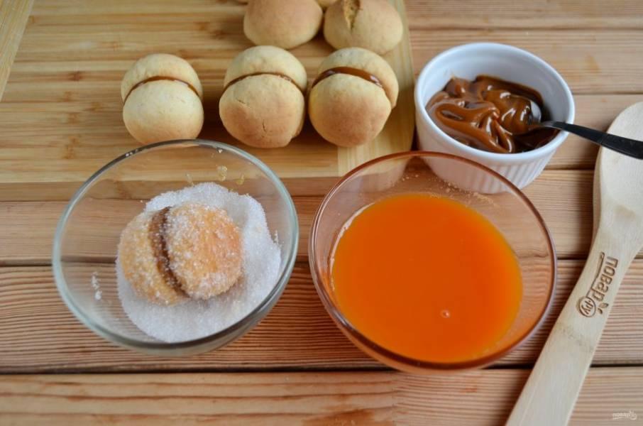 """Сгущенка должна быть холодной, из холодильника. Смажьте половинки """"абрикосок"""" сгущенкой и соедините между собой, выбирайте половинки примерно одинакового размера. Окунайте каждое пирожное сначала в морковный сок или краситель, потом обваливайте в сахаре."""