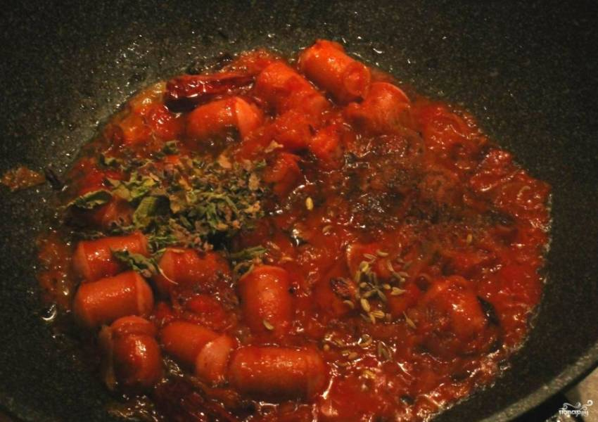 Теперь берем сардельки и снимаем с них пленку, если она не натуральная. Режем кусочками. Когда овощи обжарятся, кладем в них нарезанные сардельки, томатную пасту и зелень. Все тушим на медленном огне минут 10.