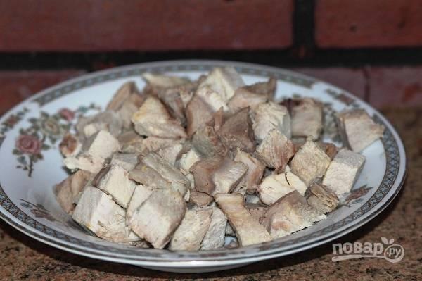 9. Когда мясо сварилось, аккуратно достаньте его и немного остудите. После нарежьте небольшими кусочками, отделив от косточки. Бульон процедите и снова отправьте на огонь.